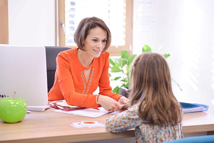 Sarah grange dans son bureau avec une jeune patiente